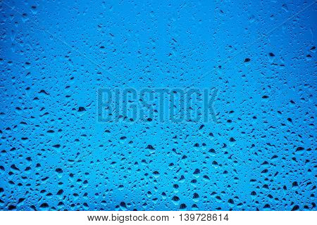 Water drops flow down on the glass in the rain on a blue background