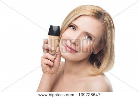 Beautiful middle aged woman with smooth skin and short blond hair holding face foundation cream. Beauty shot. Isolated over white background. Copy space.