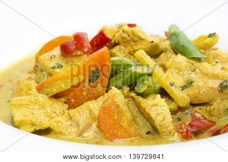 chicken curry with vegetables on a white plate in a restaurant