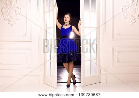 She Comes. Girl in dark blue dress open white doors and enter indoor from dark