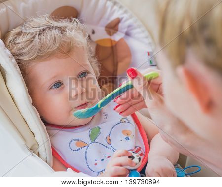 A mother feeding her baby boy with spoon outdoor.