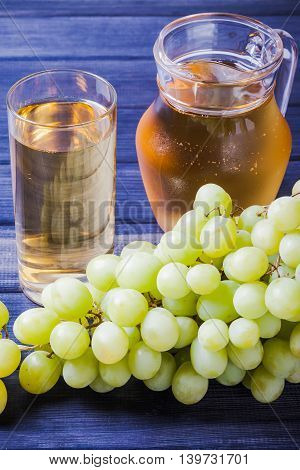 Grape juice in the glass and pitcher vertical still life