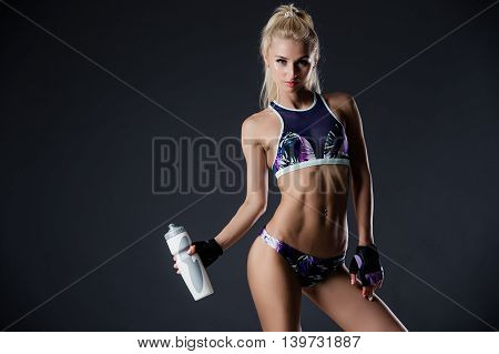 young beautiful sports girl posing with a bottle in his hand.