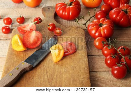 Composition of tomatoes and slices on wooden cutting board