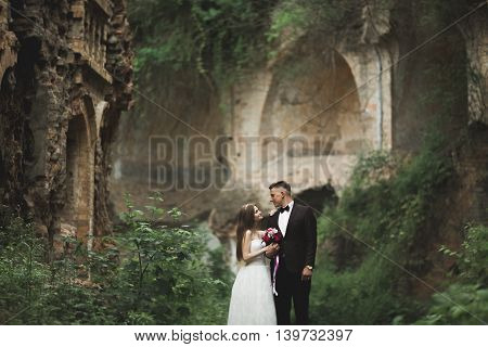 Beautiful fairytale newlywed couple hugging near old medieval castle.
