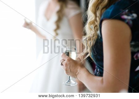 Glass of champagne in the hand of a guest during wedding reception on background the bride