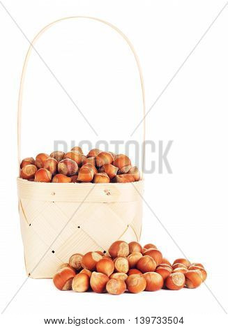 hazelnuts in wooden basket, isolated on white background