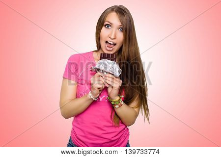 Beauty model woman eating dark chocolate. Beautiful Surprised young woman takes chocolate sweets, smiling and having fun. Funny girl, professional make up and bow hairstyle. Pink background.