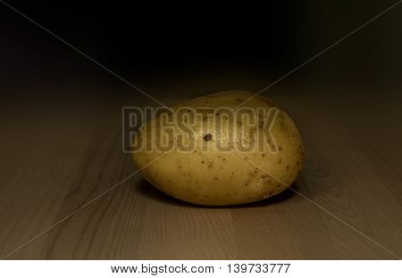 one yellow potato on wooden background , c
