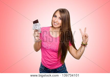 Beauty model woman eating dark chocolate. Beautiful Surprised young woman takes chocolate sweets, smiling and shows victory. Funny girl, professional make up and bow hairstyle. Pink background.