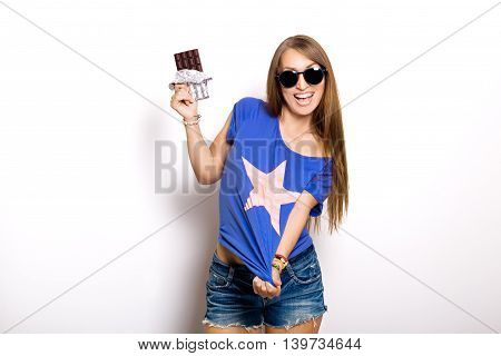 Beauty model woman in sunglasses eating dark chocolate. Beautiful Surprised young woman takes chocolate sweets, smiling and having fun. Funny girl, professional make up and bow hairstyle. Pink background.