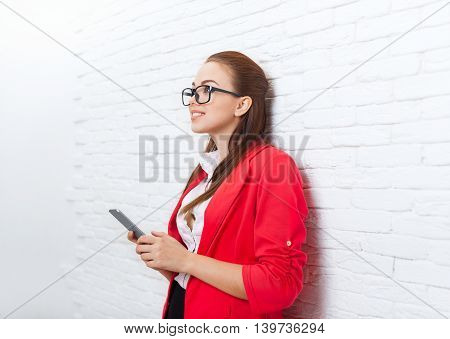 Businesswoman use cell smart phone look up to copy space wear red jacket glasses happy smile business woman over office wall