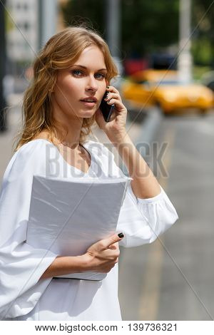 Young business woman holding documents and calling on phone on street background