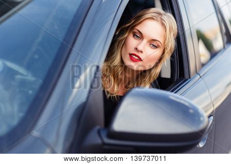 Gorgeous blonde young woman behind the wheel of car looking in side mirror