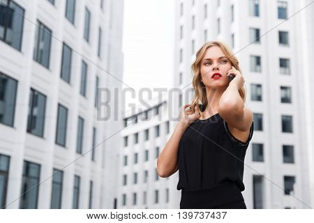 Modern business woman in black clothes negotiating on phone about important meeting