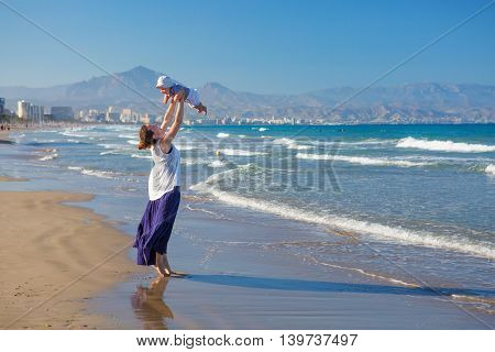 Mother And Her Son Have Fun At The Sea Beach At The Sunset