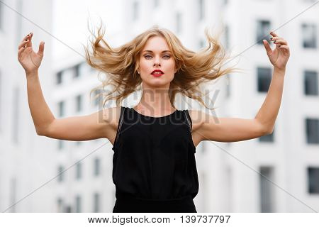 Outdoors portrait of young blond woman in motion, gesticulating with flying hair