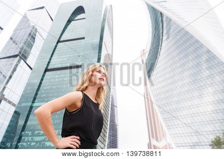 Businesswoman standing in half turn with hands on hips on street background