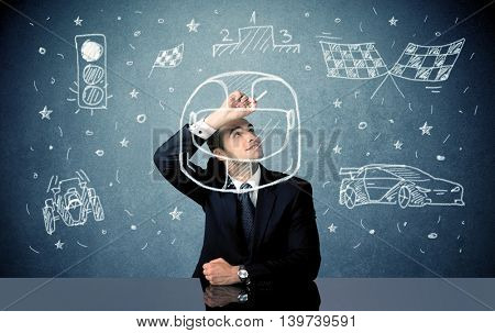 A happy businessman sitting at desk and drawing race car, flag, helmet around himself with a white chalk concept