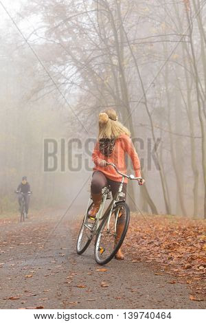 Active woman riding bike bicycle in foggy fall autumn park. Young girl in sweater and earmuffs relaxing. Healthy lifestyle and recreation leisure activity.