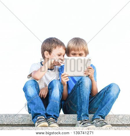 Two boys sitting and looking at tablet pc. Outdoor. Childhood, education, learning, technology, leisure concept