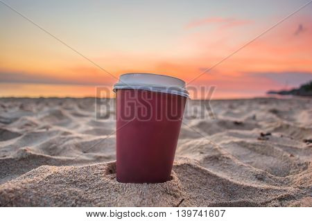 cup off coffee in plastic on sand beach and view of sunset or sunrise background. bracing morning