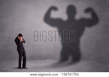 Business man looking at his own strong fit shadow concept on background