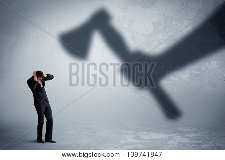 Businessman afraid of a huge shadow hand holding an axe concept on background