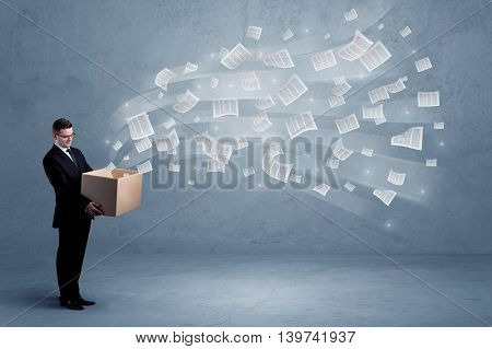 Office documents, contracts, papers flying out of cardboard box being held by a young business worker concept.
