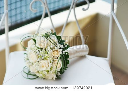 Beautiful wedding bouquet of roses on a chair