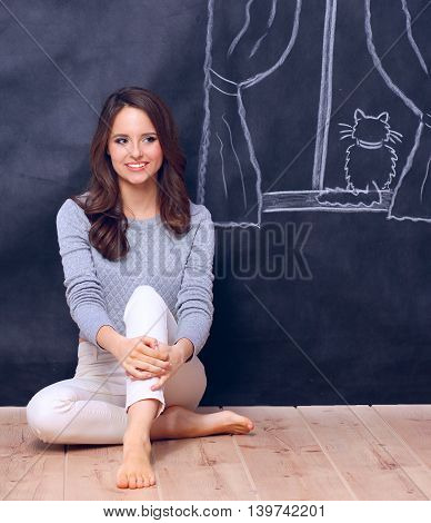 Young woman sitting on the floor near dark wall with painted a window.
