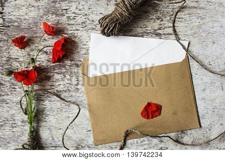 bouquet of wild red poppy flowers with rope, envelope with a card with copy space to wish on white wooden background .top view. holiday gift set