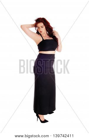 A pretty young woman standing in a long black skirt and red long hair looking away isolated for white background.