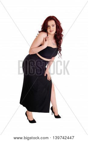 A lovely young woman in a long black dress and red hair standing isolated for white background.