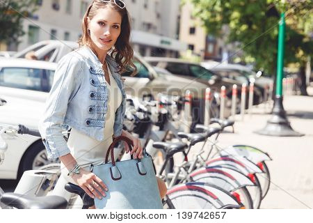 Portrait of caucasian young brunette woman in casual style sitting on bicycle next bicycle parking