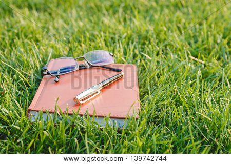 Pen, Glasses and Notebook on Fresh Green Grass. Education Concept