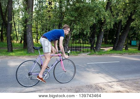 Man in shirts riding a bike in the city park in a sunny summer day