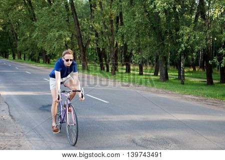 Young trendy man in sunglasses riding a bike on the asphalted road near the city park