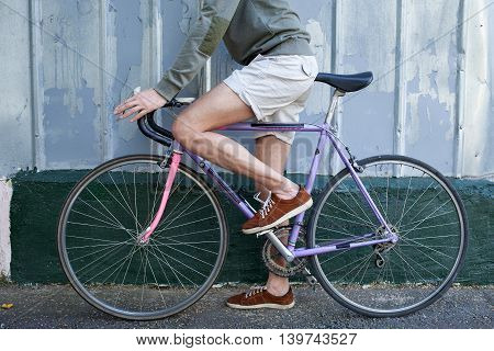 Man in shorts carrying the bike against the wall going to move