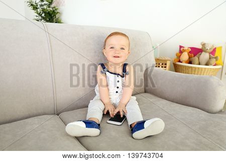 Baby playing with telephone on sofa
