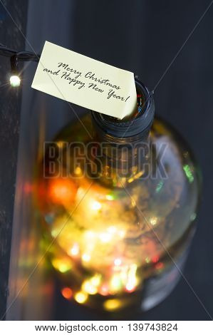 Merry Christmas and Happy New year idea, label and bottle with colored lights