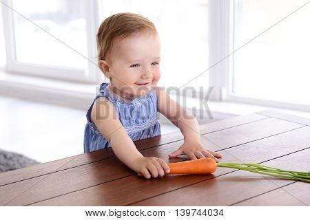 Little girl sitting at table in room with carrot