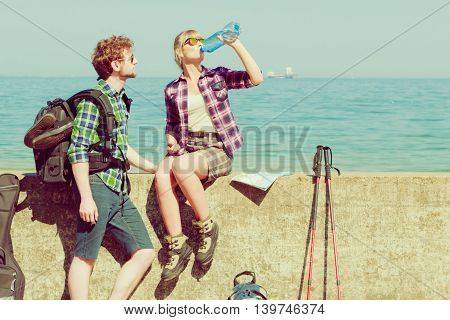 Adventure summer tourism active lifestyle. Young couple backpacker tramping by seaside girl drinking water from plastic bottle