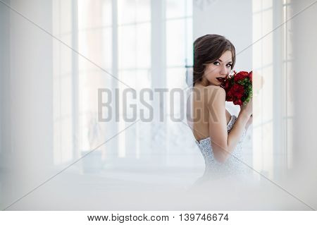 Glamorous young bride wearing wedding dress with flowers standing in front of doors indoors at luxury interior room.