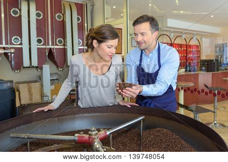 Man and lady looking at coffee beans from a vat