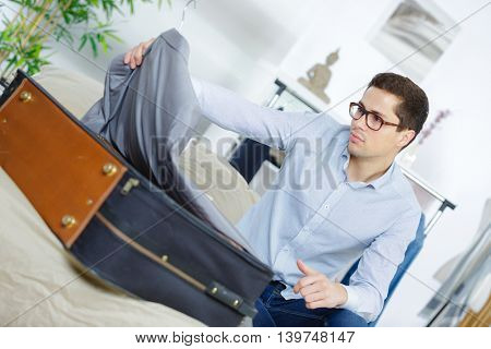 side view of a businessman unpacking luggage at a hotel