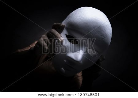 Mysterious person showing white mask in the dark,Scary background for book cover