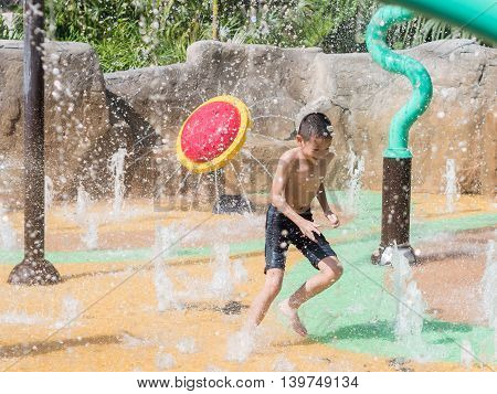 Asian child little boy having fun to play with water in park fountain in summer time