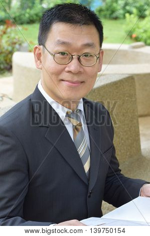 An asian business man looking at camera while holding a book