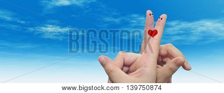 Concept or conceptual human or female hands with two fingers painted with a red heart and smiley faces over cloud blue sky background banner